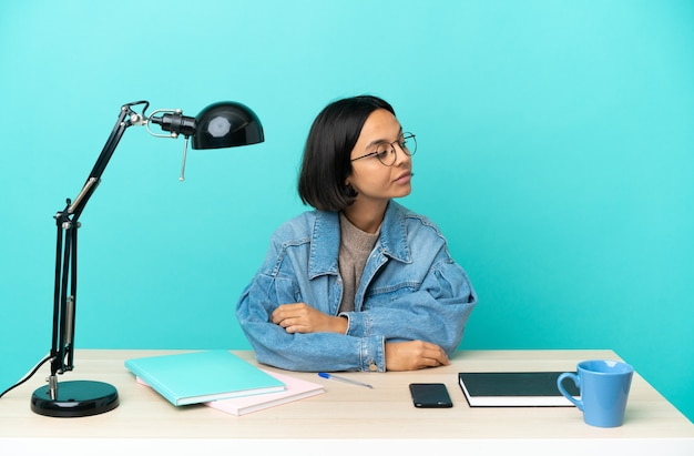 Giovane studentessa di razza mista che studia su un tavolo guardando di lato