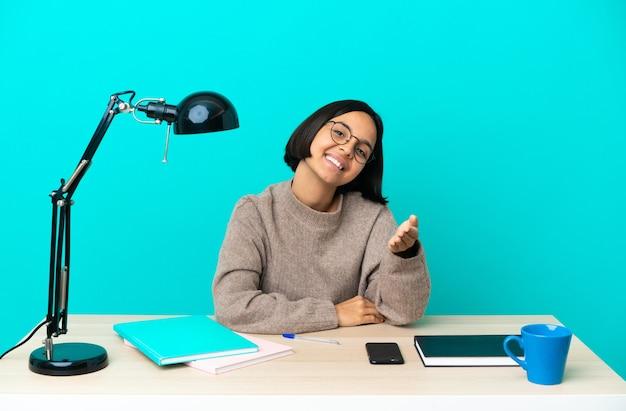 Giovane studentessa di razza mista che studia su un tavolo stringe la mano per aver chiuso un buon affare