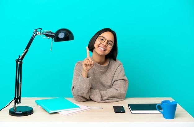 Giovane studentessa di razza mista che studia su un tavolo mostrando e alzando un dito