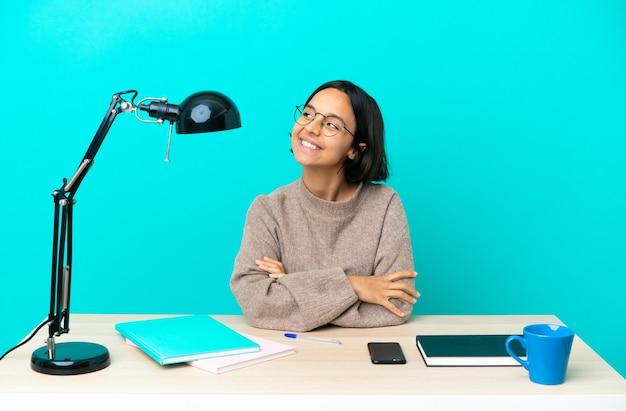 Giovane studente di razza mista donna che studia su un tavolo pensando a un'idea mentre guarda in alto