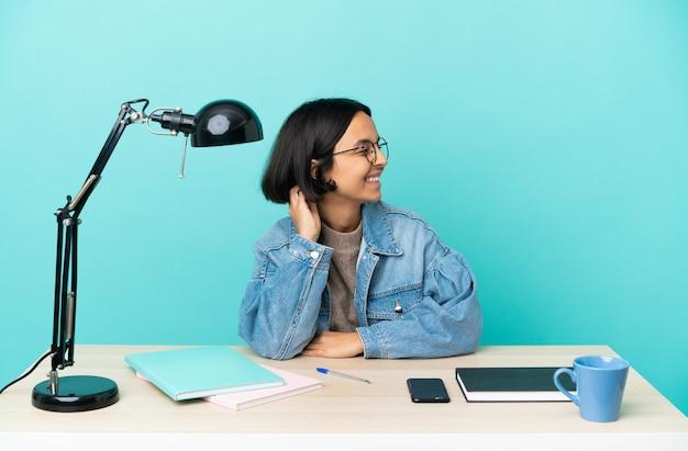 Giovane studentessa di razza mista che studia un tavolo pensando a un'idea