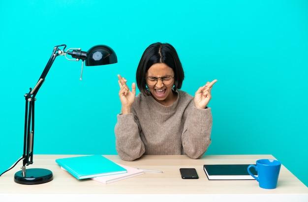 Giovane studentessa di razza mista che studia su un tavolo con le dita incrociate