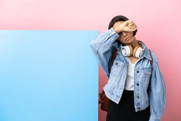 Giovane studentessa di razza mista con un grande striscione su sfondo isolato che copre gli occhi con le mani
