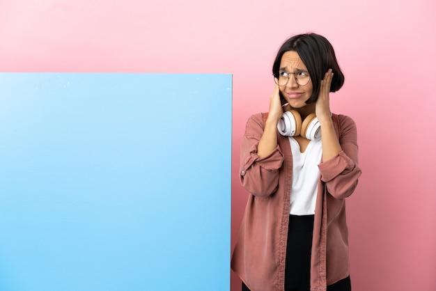 Giovane studentessa di razza mista con un grande striscione su sfondo isolato frustrata e che copre le orecchie