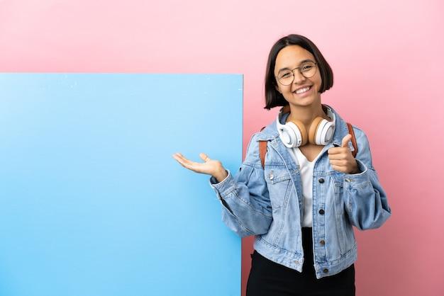 Giovane studente di razza mista donna con un grande banner su sfondo isolato tenendo copyspace immaginario sul palmo per inserire un annuncio e con il pollice in alto