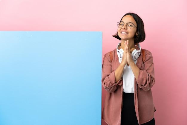 Giovane studentessa di razza mista con un grande striscione su sfondo isolato tiene insieme il palmo. la persona chiede qualcosa