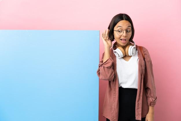 Giovane studentessa di razza mista con un grande striscione su sfondo isolato ascoltando qualcosa mettendo la mano sull'orecchio