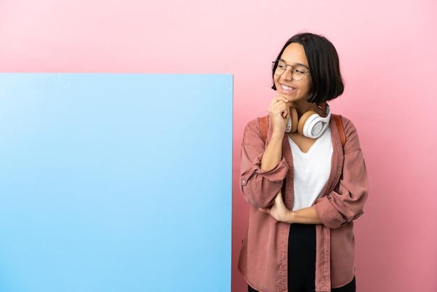 Giovane studentessa di razza mista con un grande striscione su sfondo isolato guardando di lato e sorridente