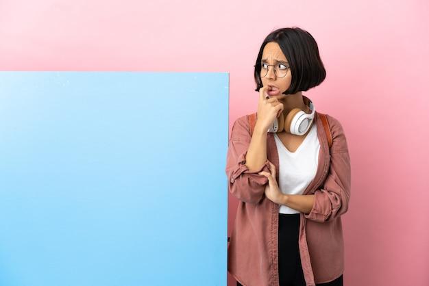 Giovane studentessa di razza mista con un grande striscione su sfondo isolato nervosa e spaventata
