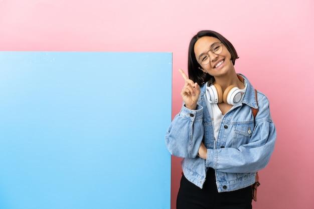 Giovane studentessa di razza mista con un grande striscione su sfondo isolato che mostra e solleva un dito in segno del meglio