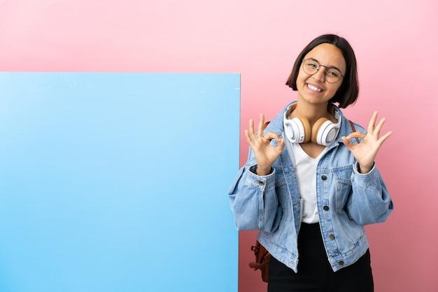 Giovane studentessa di razza mista con un grande striscione su sfondo isolato che mostra segno ok con due mani