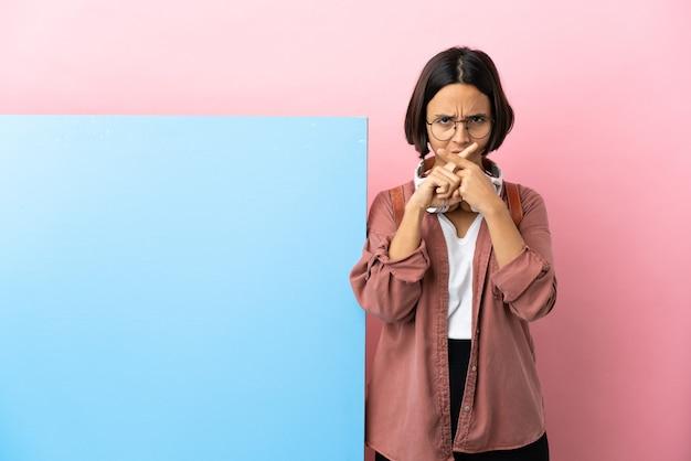 Giovane studentessa di razza mista con un grande striscione isolato sullo sfondo che mostra un segno di gesto di silenzio