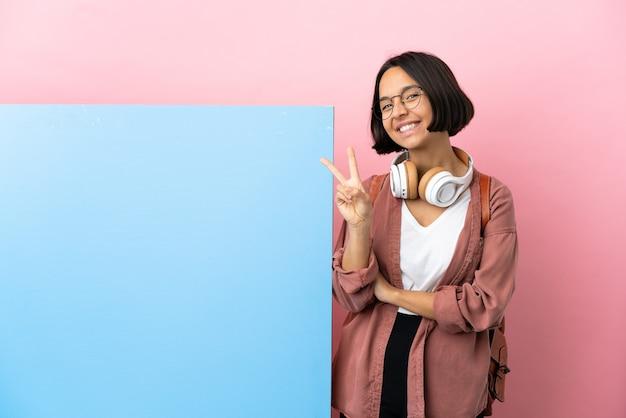 Giovane studentessa di razza mista con un grande striscione su sfondo isolato che sorride e mostra il segno della vittoria
