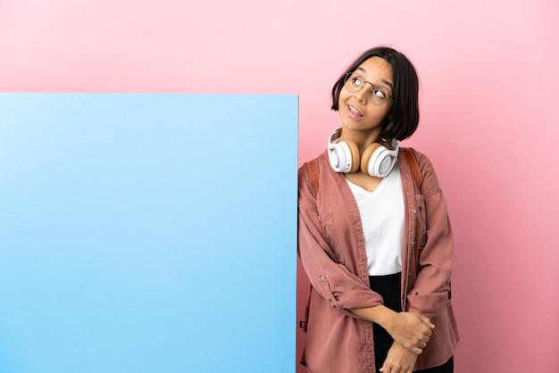 Giovane studente di razza mista donna con un grande striscione su sfondo isolato pensando un'idea mentre guarda in alto