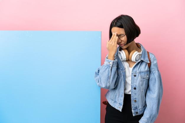 Giovane studentessa di razza mista donna con un grande striscione su sfondo isolato con mal di testa