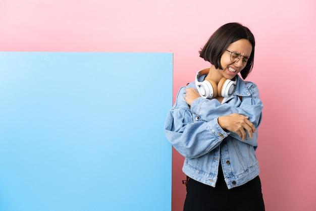 Giovane studente di razza mista donna con un grande striscione su sfondo isolato con dolore al gomito