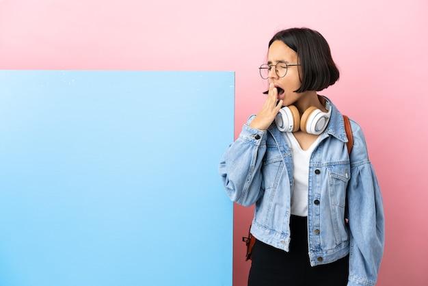 Giovane studente di razza mista donna con un grande striscione su sfondo isolato che sbadiglia e che copre la bocca spalancata con la mano