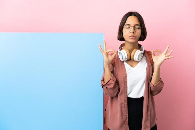 Giovane studente di razza mista donna con un grande striscione su sfondo isolato in posa zen