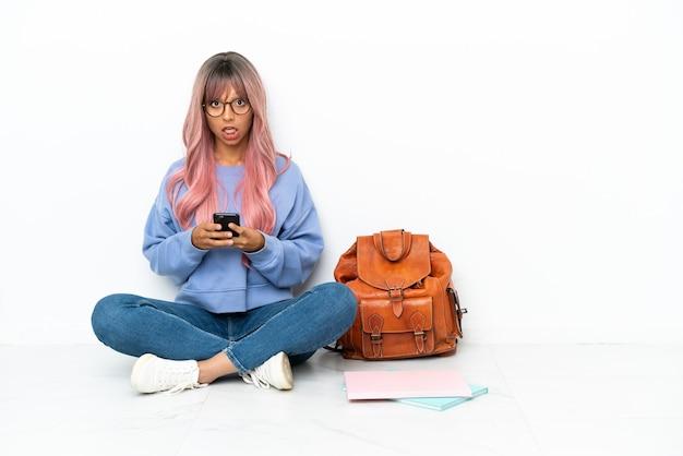 Giovane studentessa di razza mista con i capelli rosa seduta su un pavimento isolato su sfondo bianco sorpreso e inviando un messaggio