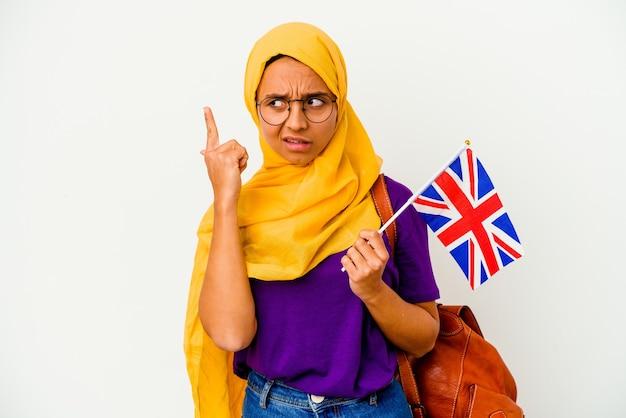 Giovane studente musulmano donna isolata sul muro bianco che punta il tempio con il dito, pensando, concentrato su un compito.