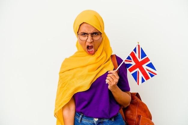 Donna musulmana del giovane studente isolata sulla parete bianca che grida molto arrabbiata e aggressiva.