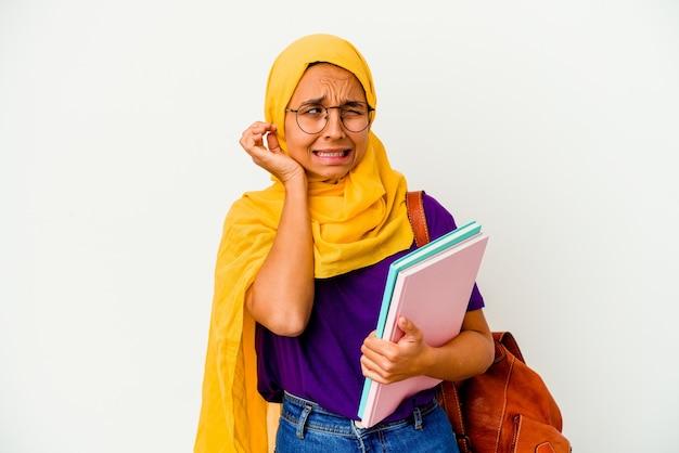 Giovane studente musulmano donna che indossa un hijab isolato su sfondo bianco che copre le orecchie con le mani.