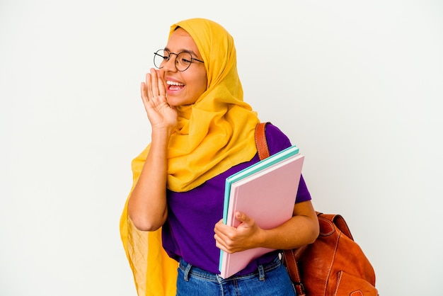 Giovane studentessa musulmana che indossa un hijab isolato sul muro bianco gridando e tenendo il palmo vicino alla bocca aperta