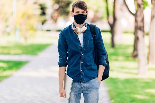Un giovane studente in una maschera medica protettiva sul suo viso cammina attraverso il parco con un computer portatile in mano