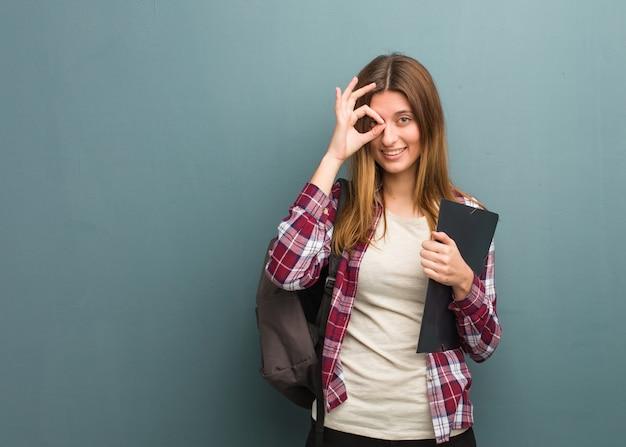 Donna russa del giovane studente fiduciosa che fa gesto giusto sull'occhio