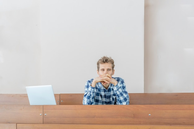 Il giovane studente si siede da solo in un'enorme aula
