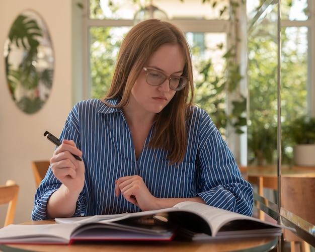 Giovane studente che studia al caffè scrivendo un programma prendendo appunti tenendo la penna e preparandosi per l'esame