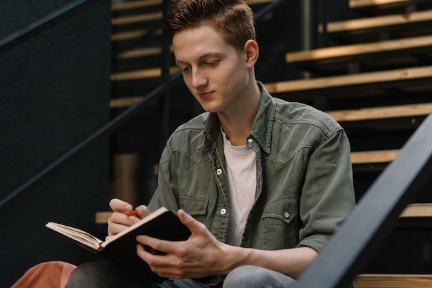 Giovane studente che studia il libro di lettura che prende appunti istruzione concept