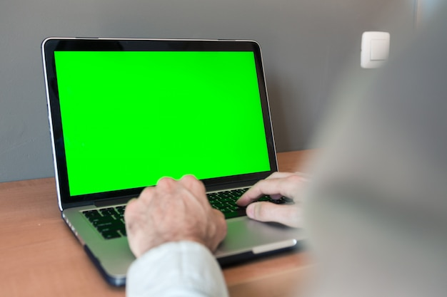 Giovane studente che studia e lavora da casa su un computer con lo schermo verde nella sua stanza.