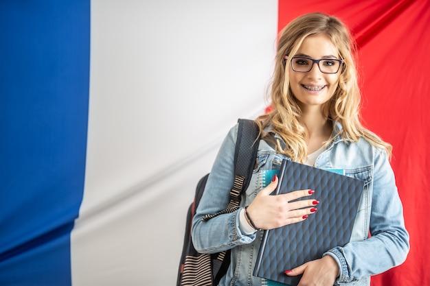Il giovane studente con le parentesi graffe tiene il libro di testo davanti alla bandiera della francia.