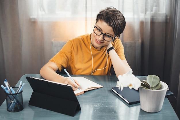 Giovane studente con gli occhiali sta tenendo lezioni online da casa utilizzando un tablet e scrivendo in un quaderno
