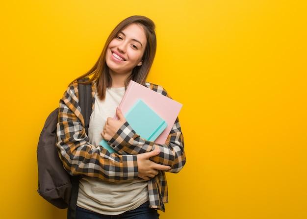 Braccia dell'incrocio della giovane donna dello studente, sorridenti e rilassate
