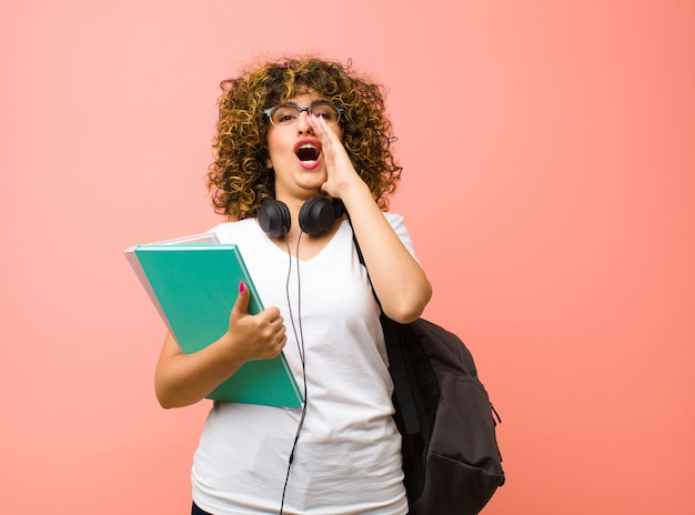 Giovane donna studente sentirsi felice, eccitato e positivo, dando un grande grido con le mani vicino alla bocca, chiamando sul muro rosa