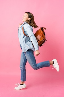 Donna giovane studente che va a scuola isolato sulla parete rosa