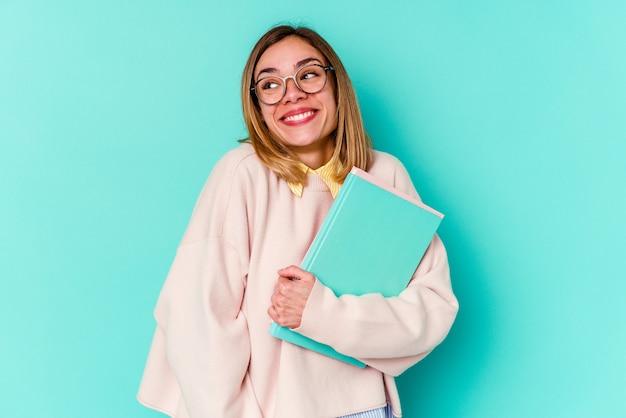 Donna giovane studente in possesso di libri isolati su blu sognando di raggiungere obiettivi e scopi