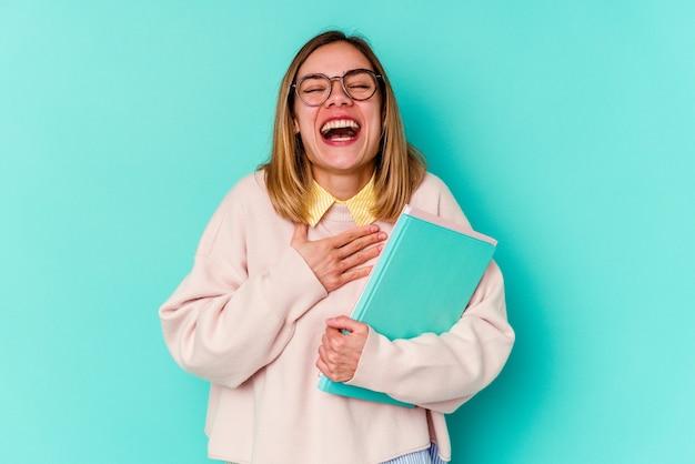 La giovane donna dell'allievo che tiene i libri isolati sull'azzurro ride ad alta voce mantenendo la mano sul petto.