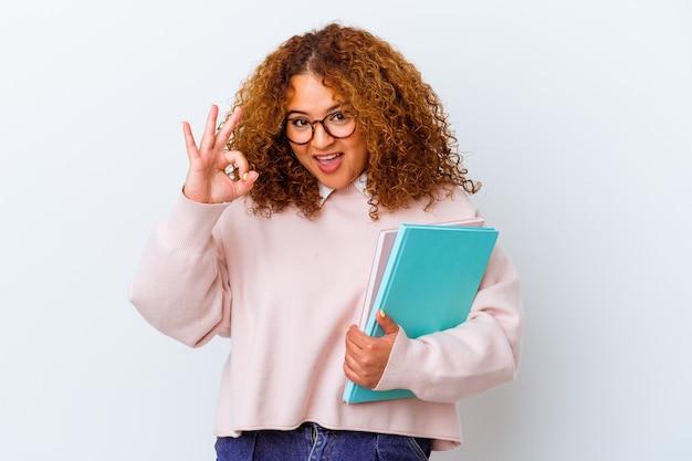 Donna giovane studente su sfondo isolato allegro e fiducioso che mostra gesto ok.