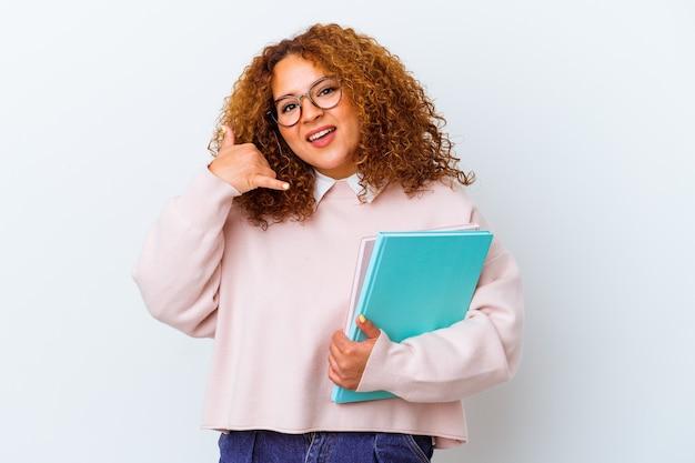 Giovane donna dello studente sopra fondo isolato che mostra un gesto di chiamata del telefono cellulare con le dita.
