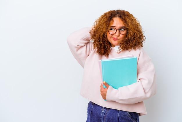 Giovane studentessa su sfondo isolato toccando la parte posteriore della testa, pensando e facendo una scelta.