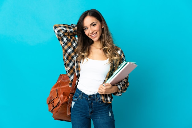 Donna giovane studente isolata su sfondo blu ridendo
