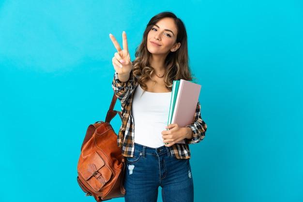 Donna giovane studente isolata su sfondo blu sorridendo e mostrando il segno di vittoria