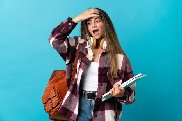 Giovane donna dello studente isolata sul gesto di sorpresa facente blu mentre guardando al lato