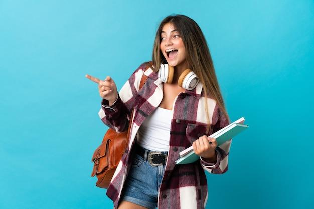 Donna giovane studente isolata sul dito puntato blu al lato e presentando un prodotto