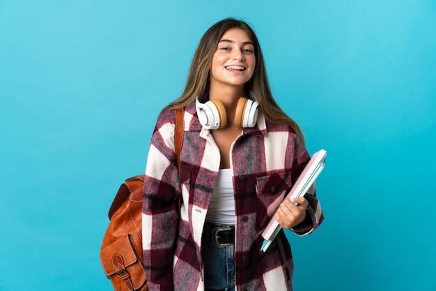 Giovane donna dello studente isolata sulla posa blu con le armi all'anca e a sorridere