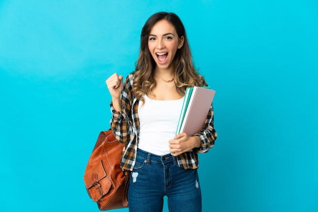 Donna giovane studente isolata sulla parete blu che celebra una vittoria nella posizione del vincitore