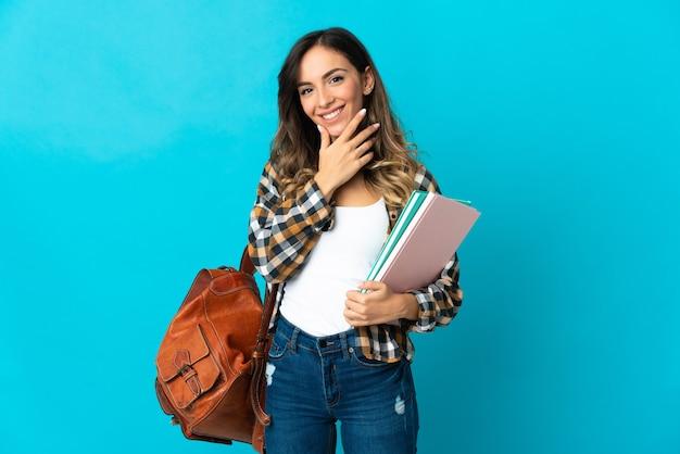 Donna giovane studente isolata sulla parete blu felice e sorridente